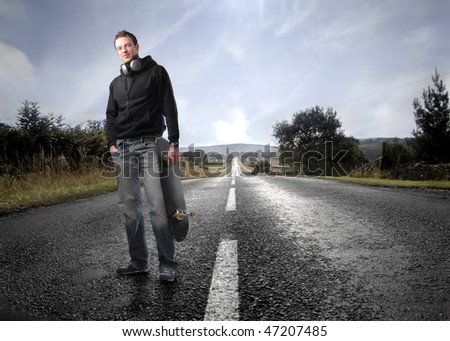 Portrait of a man standing on a countryside road with a skateboard in his hand - stock photo