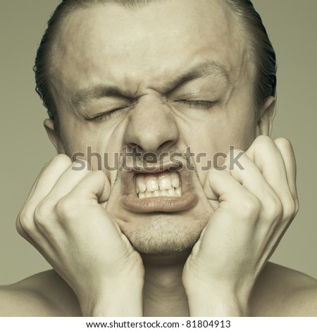 portrait of a man stretching his face - stock photo