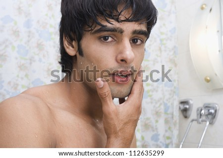 Portrait of a man touching his face after shave - stock photo