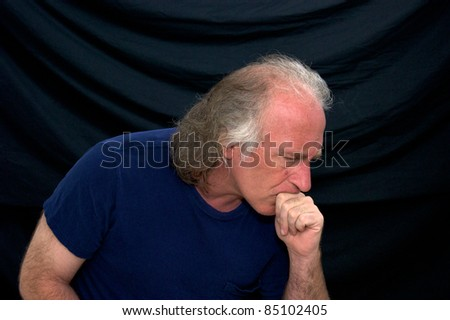 Portrait of a man turned to the side and looking concerned with his hand to his mouth. - stock photo