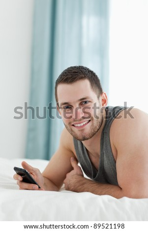 Portrait of a man using his mobile phone in his bedroom - stock photo