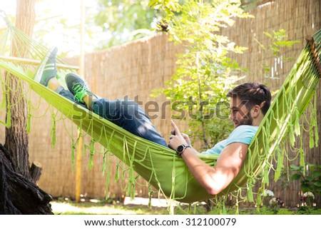 Portrait of a man using smartphone on hammok outdoors - stock photo