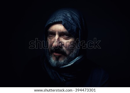 Portrait of a man wearing a headscarf.