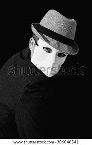Portrait of a man wearing a suit and white masquerade mask - stock photo