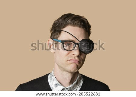 Portrait of a man wearing eye patch on glasses over colored background - stock photo
