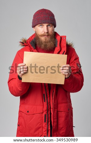 Portrait of a man wearing red winter Alaska jacket showing big envelope - banner with copy space for text, looking at camera - stock photo