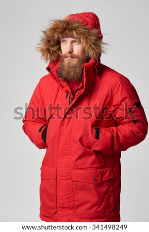 Portrait of a man wearing red winter Alaska jacket  with fur hood on,  looking forward out of frame, studio shot - stock photo