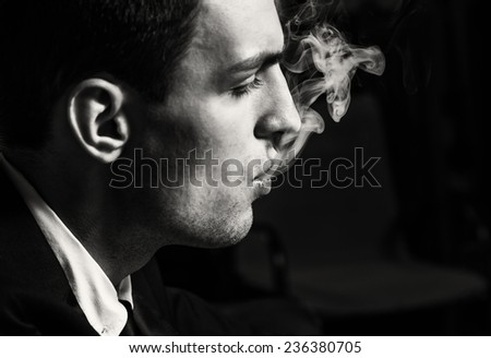 Portrait of a man who smokes, studio shooting, black and white - stock photo