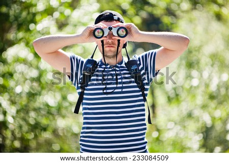 Portrait of a man with a backpack and walkie-talkies, looking through binoculars - stock photo