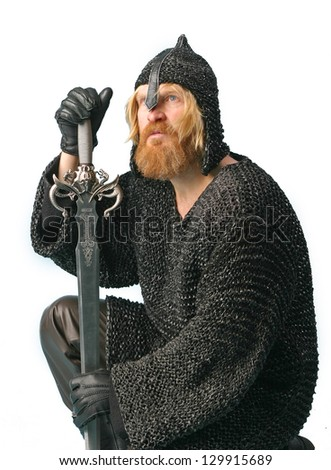 portrait of a man with a beard and mustache, a soldier in chain mail and a helmet with a sword on a light background crouched