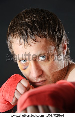 Portrait of a man with a black eye in a battle position. Clenched fists. Dark background.