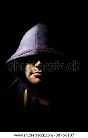 Portrait of a man with a cowl covering his eyes. Studio lighting. Half face illuminated, half face in shadows.