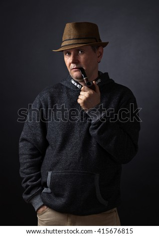 Portrait of a man with a smoking pipe , studio shot