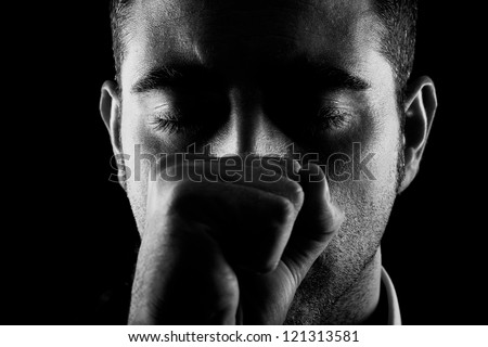 Portrait of a man with fist and eyes closed on black background - stock photo