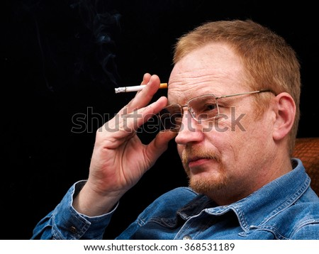 Portrait of a man with glasses and a cigarette. The man's face coarsely. His hair and beard red. Blue shirt, jeans. black Background - stock photo