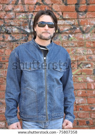 Portrait of a man with glasses in the background of an old brick wall