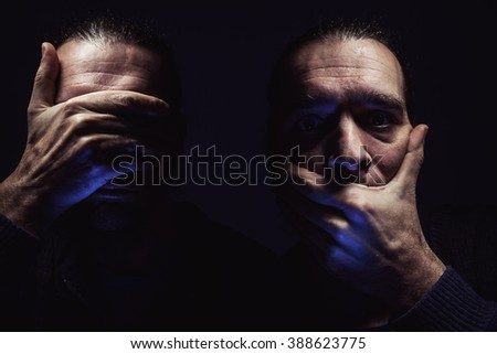 Portrait of a man with hands on eyes and mouth, conceptual composition about freedom and human rights.  - stock photo