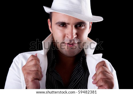 Portrait of a man with his white hat and coat, isolated on black. Studio shot - stock photo