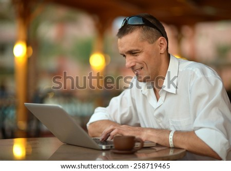 Portrait of a  man with laptop on table - stock photo