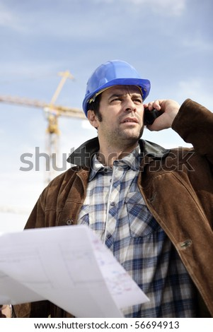 Portrait of a man with safety helmet and mobile phone - stock photo