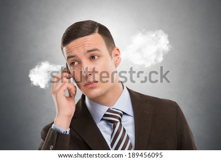Portrait of a man with steam from his ears calling by mobile phone - stock photo