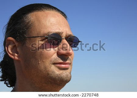 Portrait of a man with sunglasses (beach, waterdrops on his skin , blue sky) - stock photo