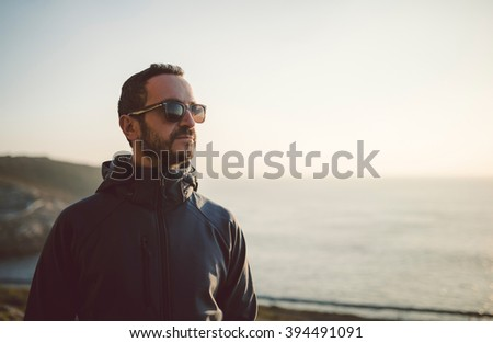 Portrait of a man with sunglasses outdoors - stock photo