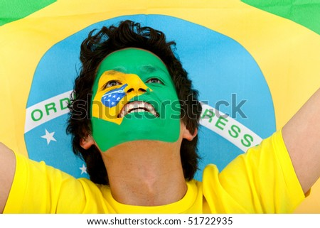 Portrait of a man with the brazilian flag painted on his face - stock photo