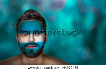 Portrait of a man with the flag of the Argentina painted on his face  - stock photo