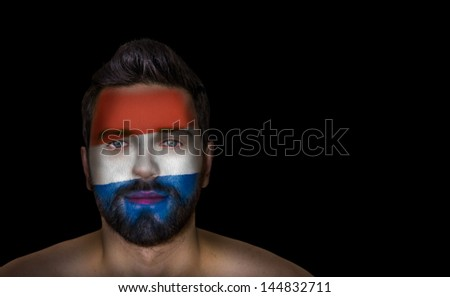 Portrait of a man with the flag of the Netherlands painted on his face - stock photo