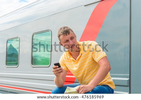 portrait of a man with the phone near long-distance trains