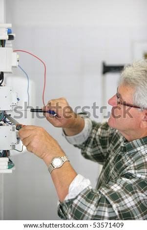 Portrait of a man working on a circuit breaker - stock photo