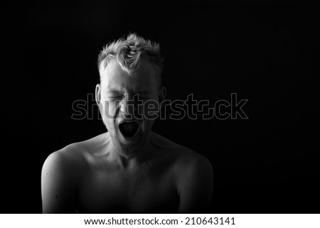 Portrait of a man yawning on black background; monochrome - stock photo