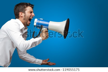 Portrait Of A Man Yelling Into A Megaphone Against Blue Background - stock photo