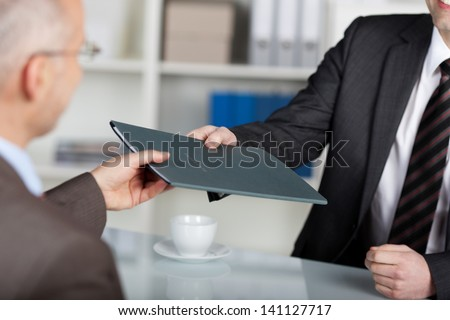 Portrait of a manager giving folder to a male applicant in his office