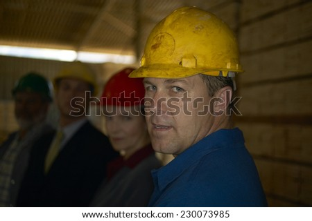 Portrait of a manual worker posing for the camera with a hard hat on - stock photo