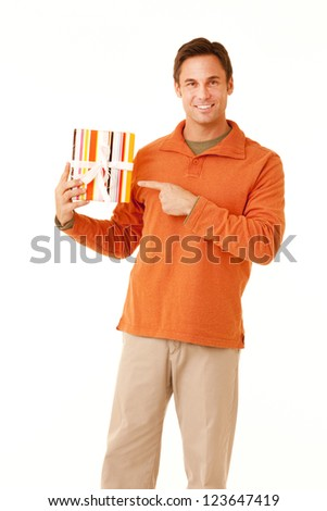 Portrait of a mature adult man wearing an orange sweater and khakis holding a wrapped gift isolated on white isolated on white - stock photo
