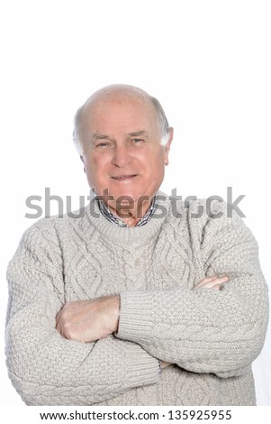 Portrait of a mature balding man, dressed in a knit sweater with arms crossed. - stock photo