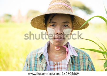 Portrait of a mature Burmese female farmer with thanaka powdered face who works in the field.