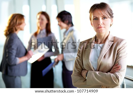 Portrait of a mature business lady standing in the foreground, her female colleagues having a talk in the background - stock photo