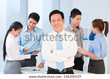 Portrait of a mature business leader standing and smiling on the foreground - stock photo