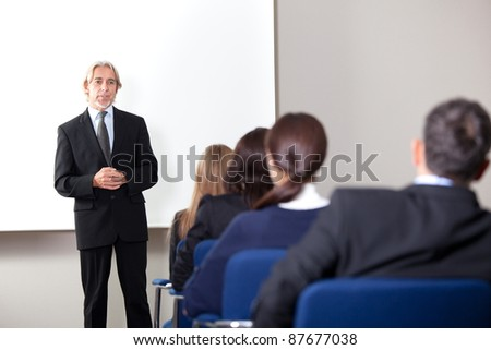 Portrait of a mature business man giving business training at a modern office - stock photo