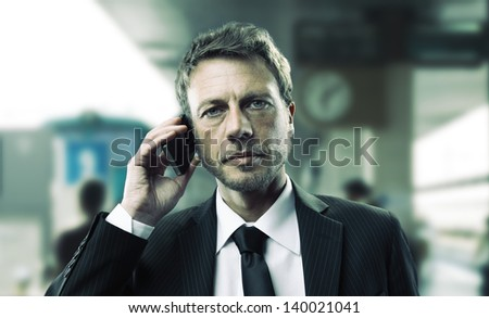 Portrait of a mature business man talking on phone at train station - stock photo
