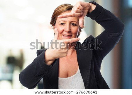 portrait of a mature business woman doing a frame gesture - stock photo