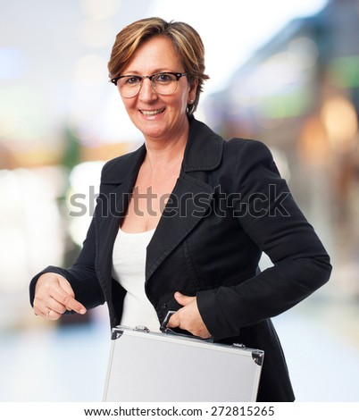 portrait of a mature business woman holding a suitcase - stock photo