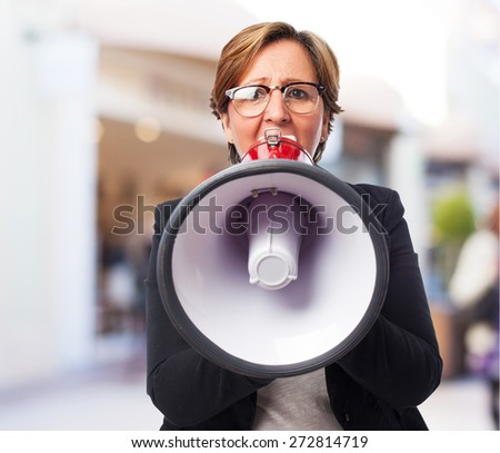 portrait of a mature business woman shouting with a megaphone - stock photo