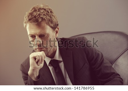 Portrait of a mature businessman looking dowm worried - stock photo