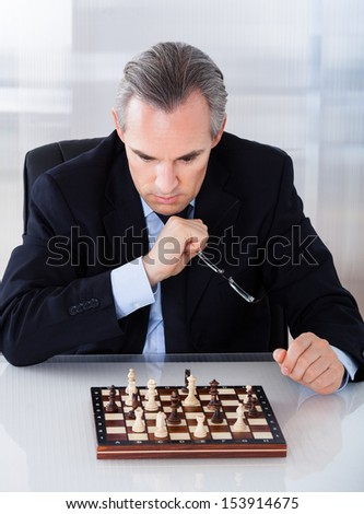 Portrait of a mature businessman playing chess - stock photo
