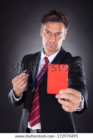 Portrait Of A Mature Businessman Showing Red Card Black Background - stock photo