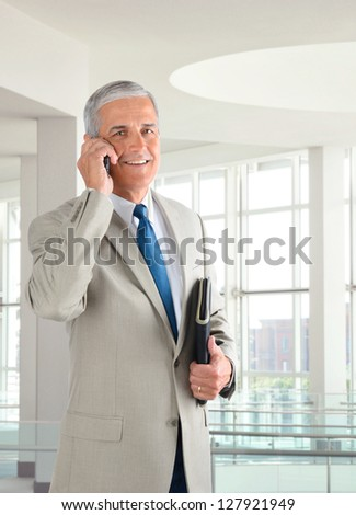 Portrait of a mature businessman standing in a modern office talking on a cell phone.. Man is holding a small binder and smiling at the camera. - stock photo